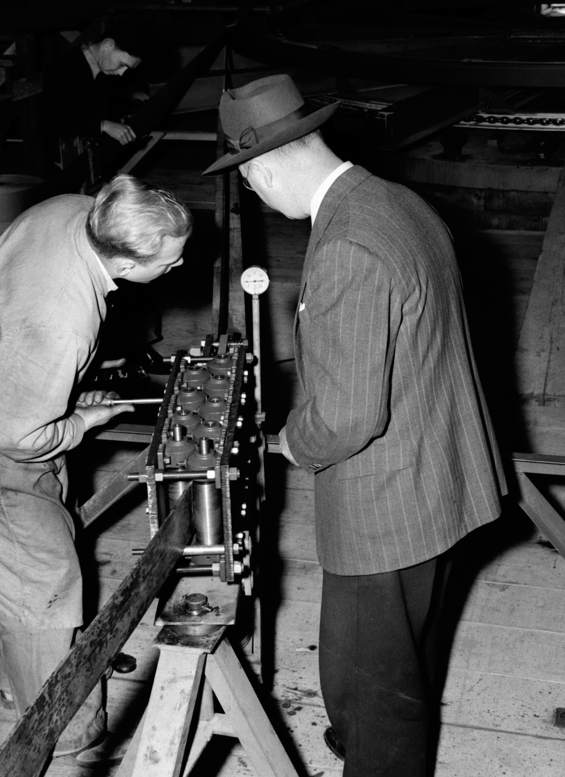 """William C. Twitchell (left) and Wallace B. Reynolds at 184-inch cyclotron coil winding """"leveler"""" straightening copper, taken March 8, 1942. Principal Investigator/Project: Analog Conversion Project [Photographer: Donald Cooksey]"""