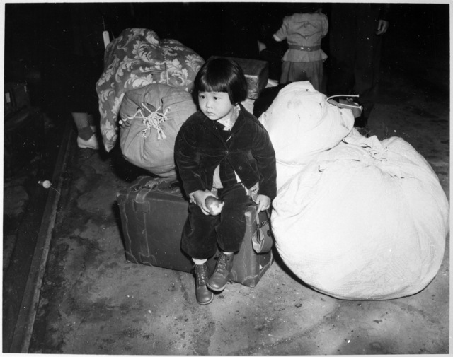 """""""A young evacuee of Japanese ancestry waits with the family baggage before leaving by bus for an assembly center in the spring of 1942."""""""