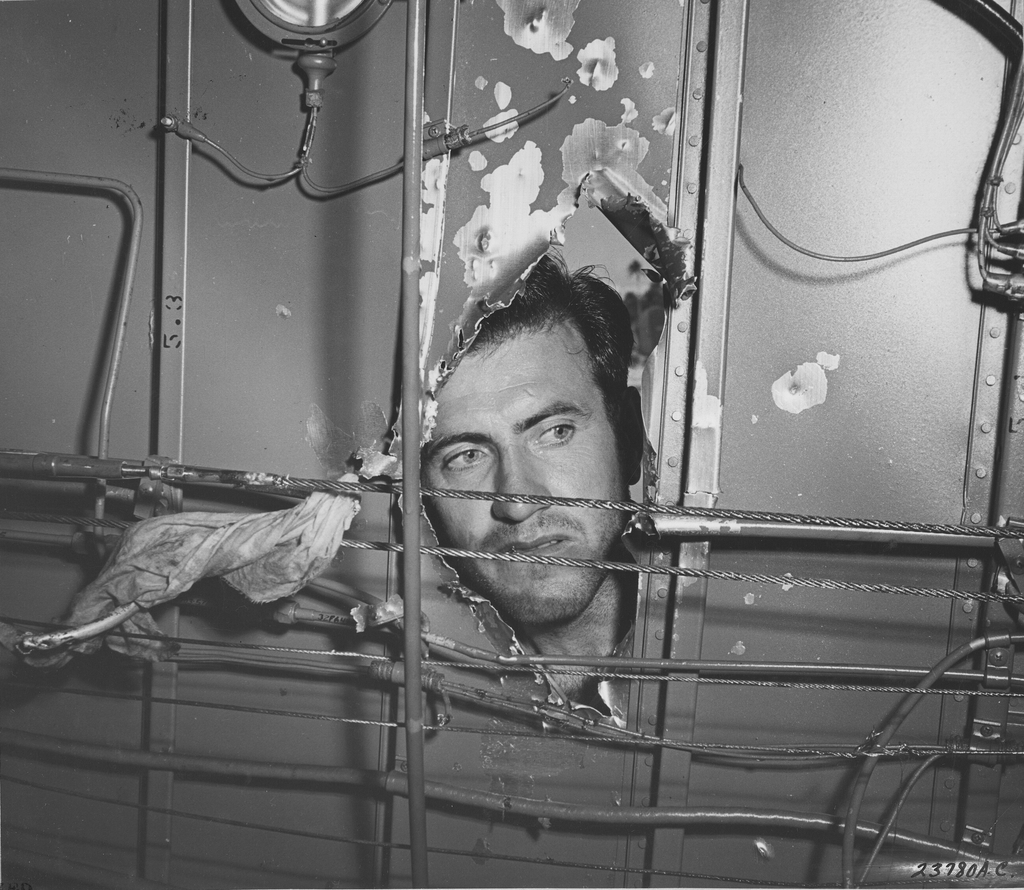 Photograph of Lt. Lou Zamperini, Bombardier, Examining the Damage a Japanese Cannon Shell did to His Liberator