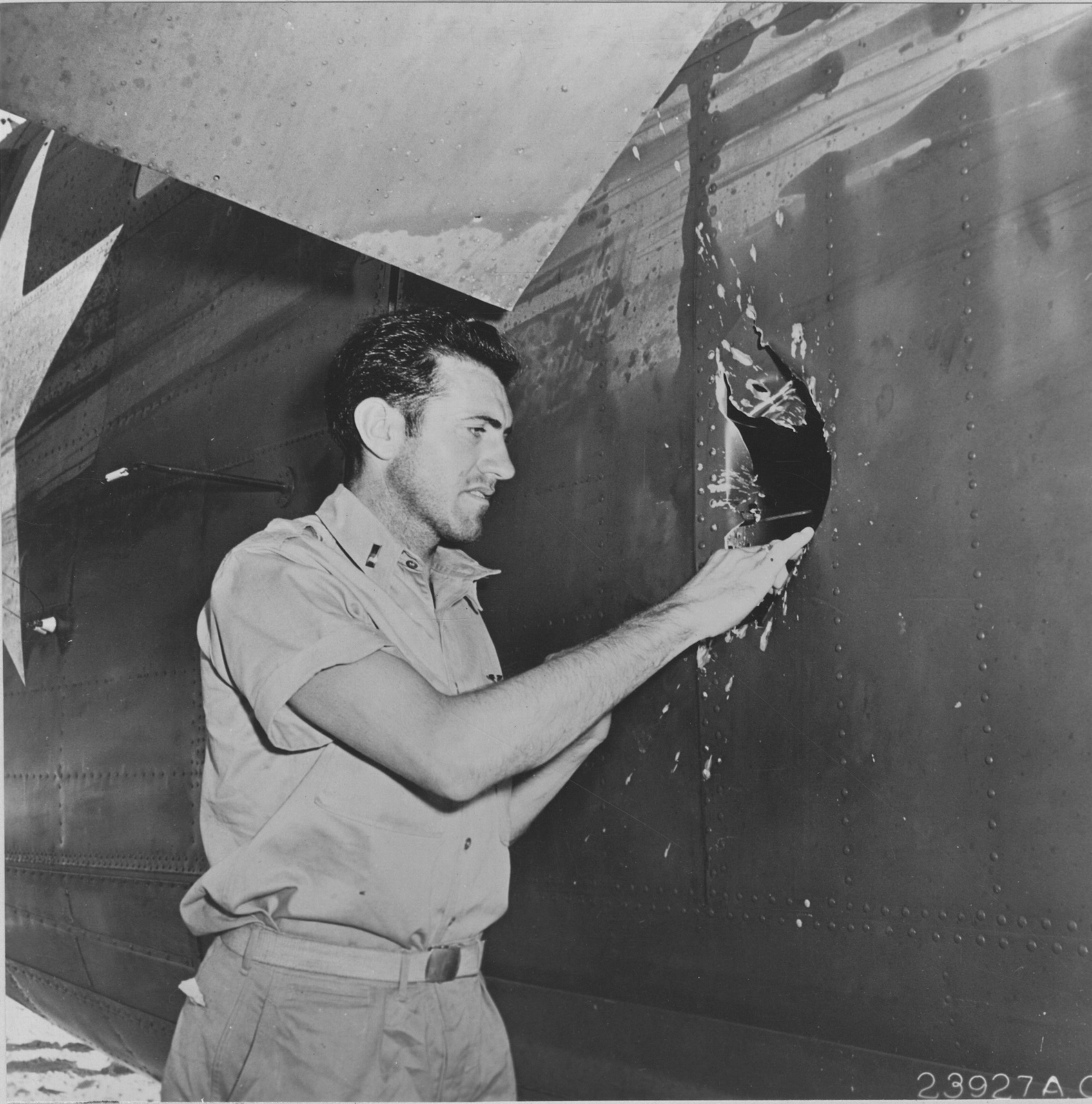 Photograph of Lt. Louis Zamperini, Former NCAA [National Collegiate Athletic Association] Miler and Olympic Team Member, Bombardier, on Lt. Russel A. Phillips' Plane, Examining 20 mm Japanese Explosive Shell Hole in the Side of Fuselage