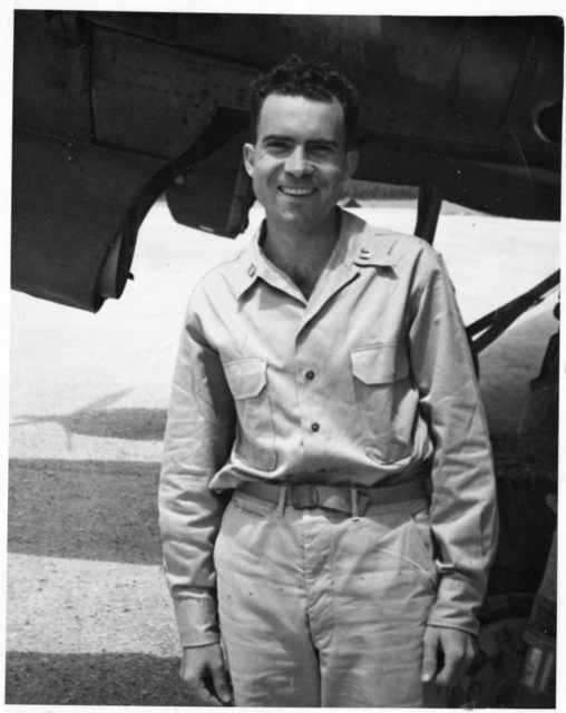 Richard Nixon in Naval uniform stands in front of a military aircraft in Espiritu Santo (South Pacific)