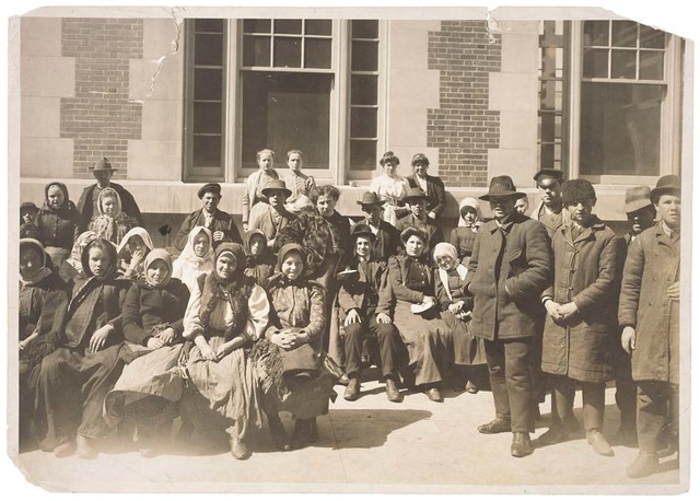 Photograph of a Group of Immigrants Outside a Building on Ellis Island