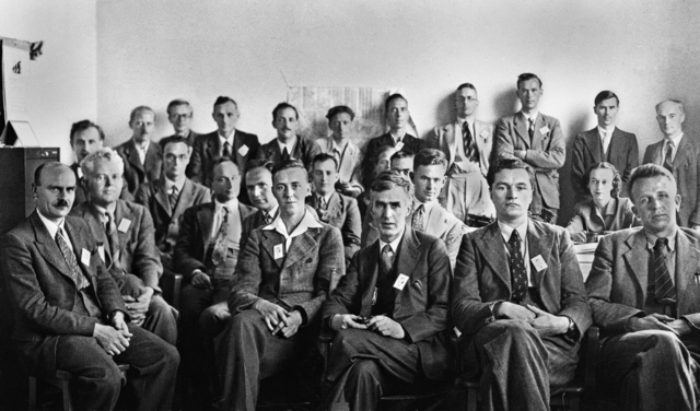 British Group associated with the Manhattan Project (Mark Oliphant Group), Nuclear Physics Research Laboratory, University of Liverpool, Mount Pleasant, Liverpool. Photo taken in 1944.  From left to right seated: H.W.S. Massey,Sir Mark L. Oliphant, R.H.V. Dawton, E.H.S Burhop, J.P. Keene, George Page, H.W.B. Skinner, S.C. Curran (mostly obscured behind Watt), C.S. Watt (mostly obscured behind Williams), R.M. Williams, S. Rowlands, Jean A. Sutherland, and M.J. Moore. Left to right standing: S.M. Duke, H.J. Morris, M.H.F. Wilkins, P.P. Starling, M.E. Haine, D.F Stanley, M.P. Edwards, J.D. Craggs, J. Sayer, W.D. Allen, T.E. Allibone.  Morgue 1944-104 (P-1) [Photographer: Donald Cooksey]