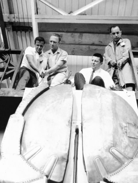 Down from their place of honor on a Crocker Lab wall come the original dees of the 60-inch cyclotron, replaced during an overhaul in 1944. Attaching the cables for the move are Crocker scientists, left to right: Mike Scardigno, Bob Druet, Bart Jones, and John Francis. Dees will remain at Lawrence Radiation Lab. Morgue 1962-87 (P-1) [Photographer: Donald Cooksey]
