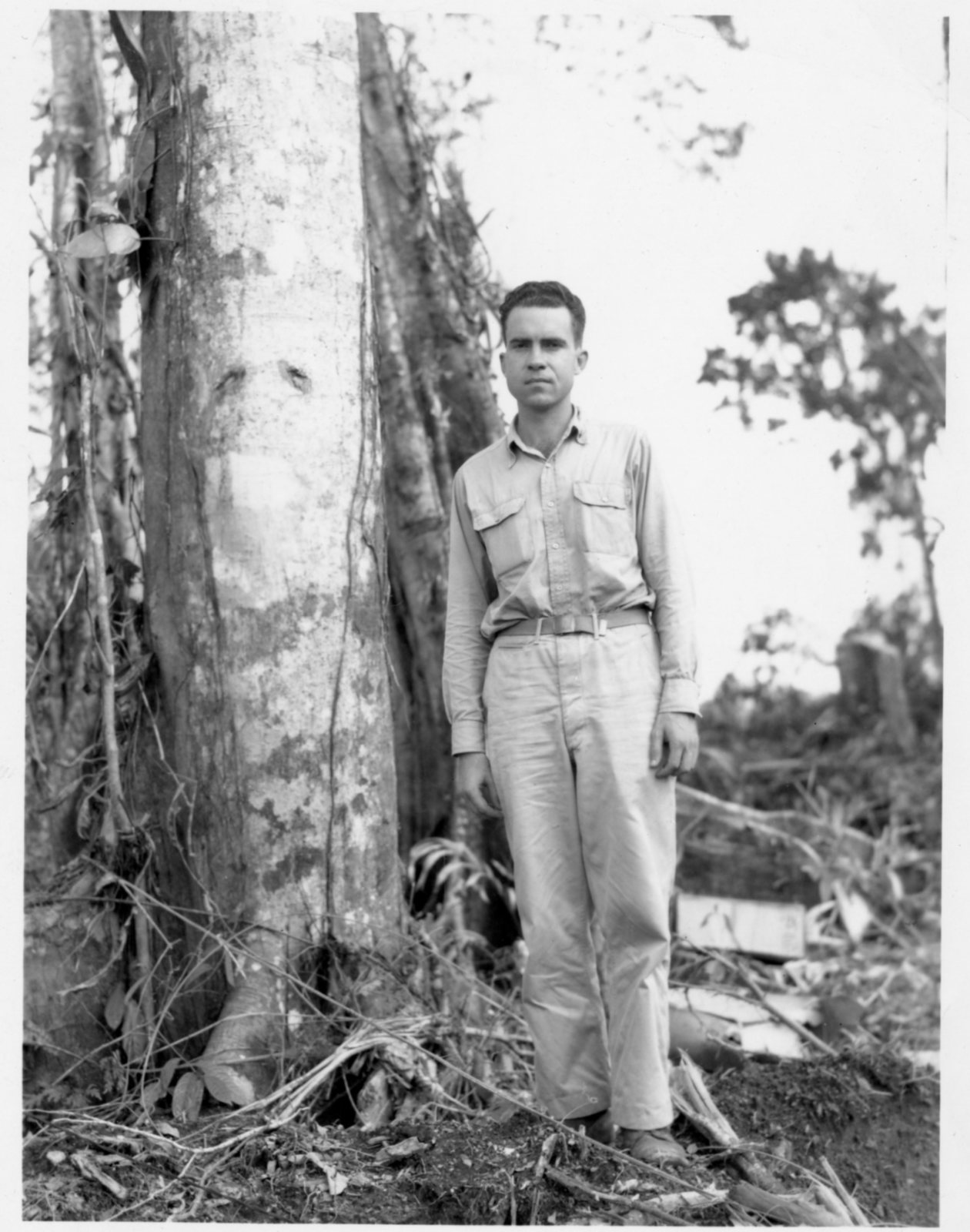 Richard Nixon stands in Naval attire by the side of a tree in the South Pacific