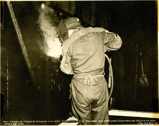 Mrs. Harvey W. Moore, Jr., Welds the Sponsor's Christening Plate to the USS Spikefish