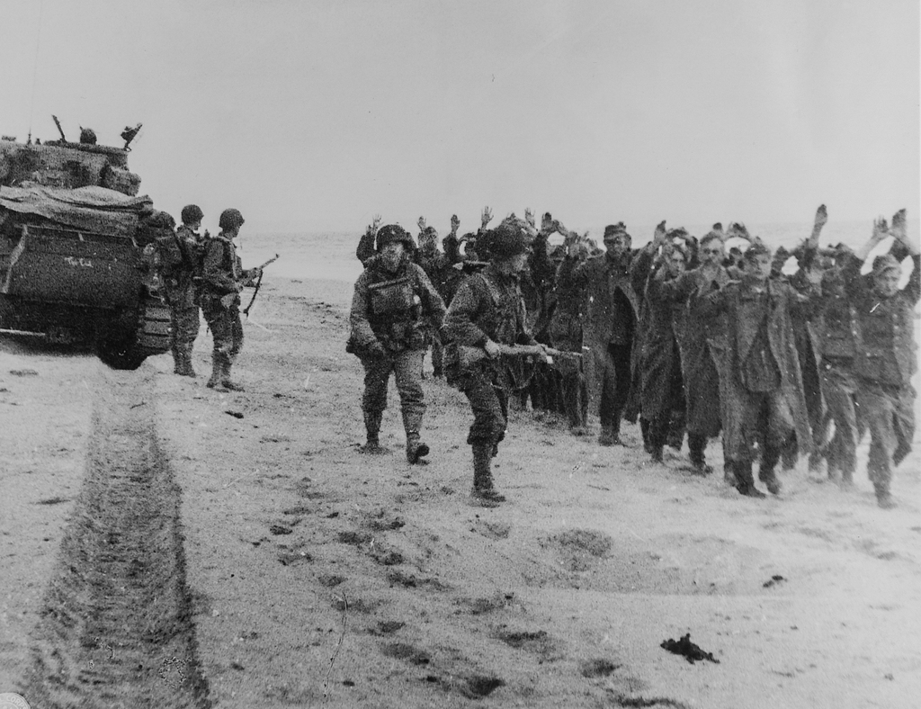 Photograph of American Soldiers Marching a Group of German Prisoners along a Beachhead in Northern France