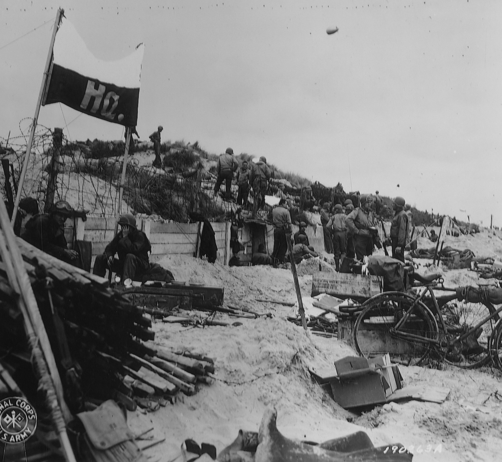 Photograph of Men and Equipment Scattered about a Command Post on Red Beach, France
