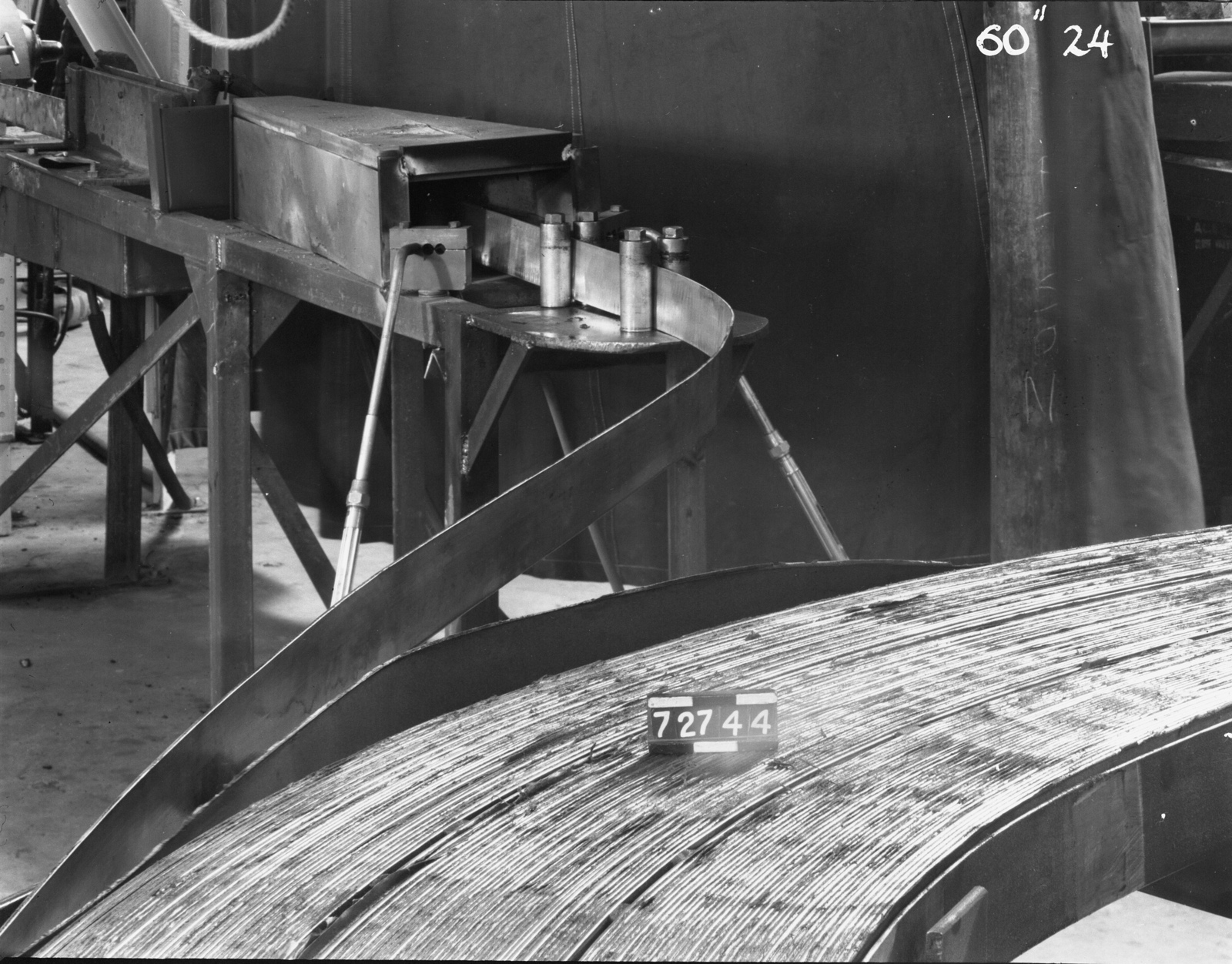 """Progression of copper into annealing furnace from old coil, 60-inch cyclotron. Photo taken 7/27/1944. 60""""-24 Principal Investigator/Project: Crocker Lab/60-inch"""