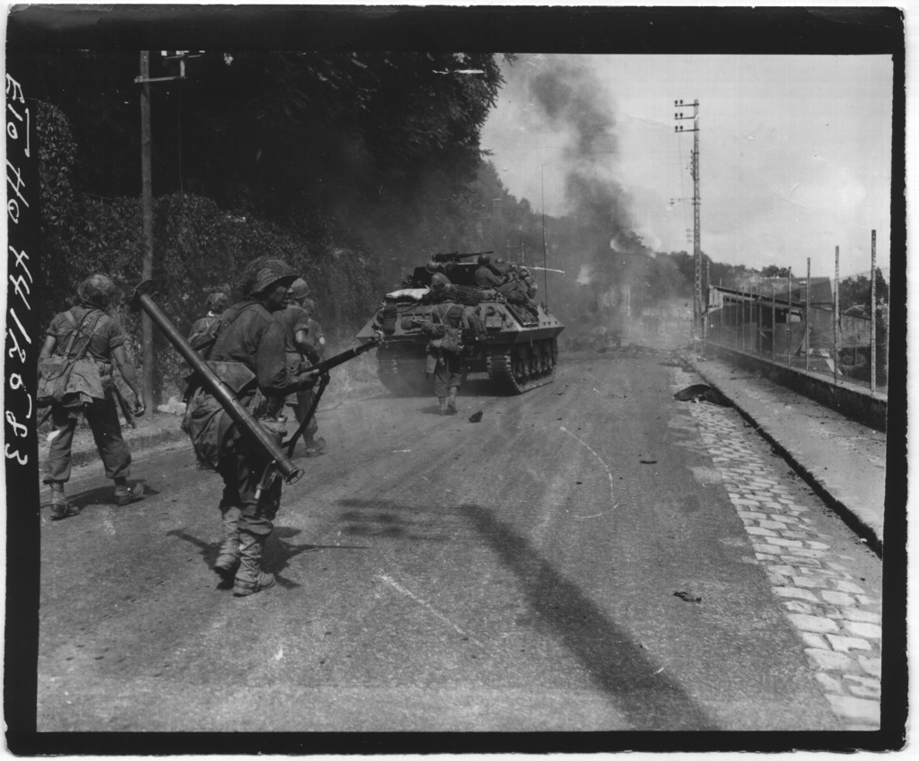 With Smoke From Blasted German Armor Filling the Sky, These American Troops Move on Toward Fontainebleau Enroute to Paris, France