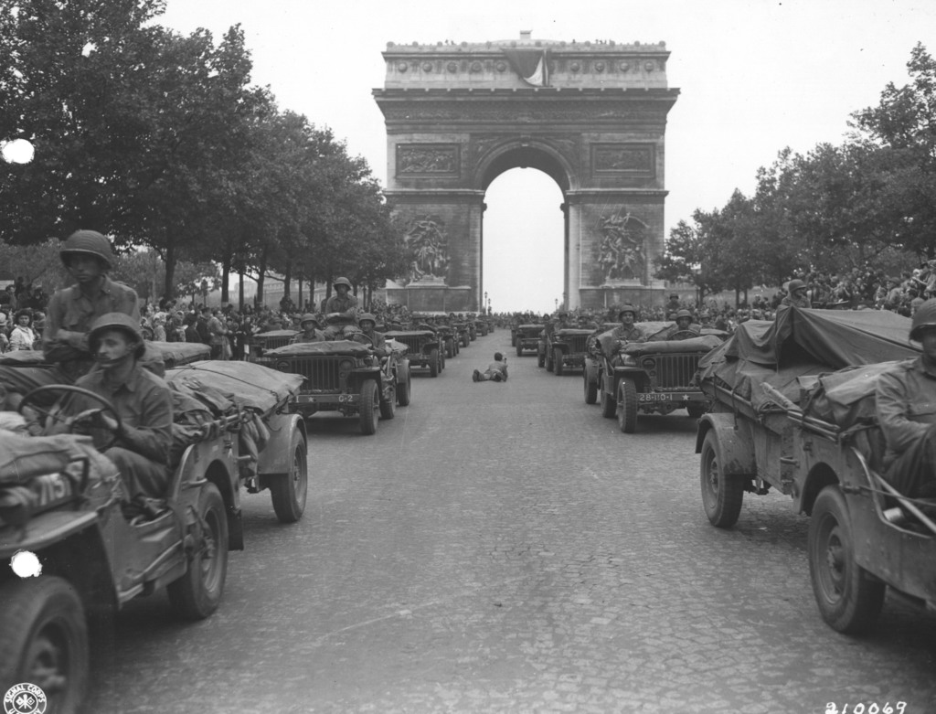 Photograph of Jeeps of the American 28th Infantry Division Moving Down the Champs Elysees in Paris, France
