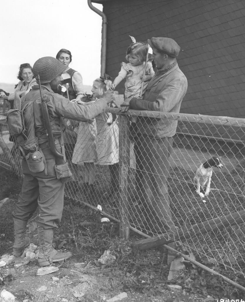 Photograph of Private Eugene V. Webber Handing a Little Girl a Stick of Chewing Gum in the Town of Asselbourn, Luxemburg