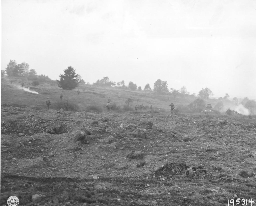 Photograph of American Infantrymen Racing across an Open Field to Reach a German Pillbox