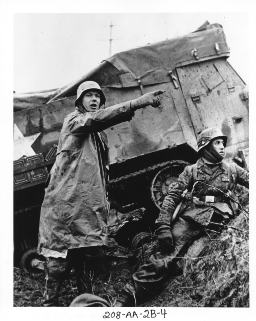 Photograph taken from a Captured German Film Showing a Nazi Soldier beside a Disabled American Half-Track