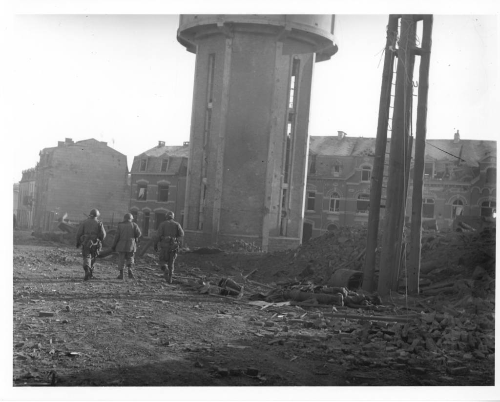 Photograph of Members of the 101st Airborne Division as they Walk Past Dead Comrades