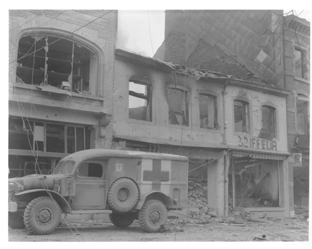 Photograph of an American Ambulance Waiting outside of a Bombed Building in Bastogne, Belgium