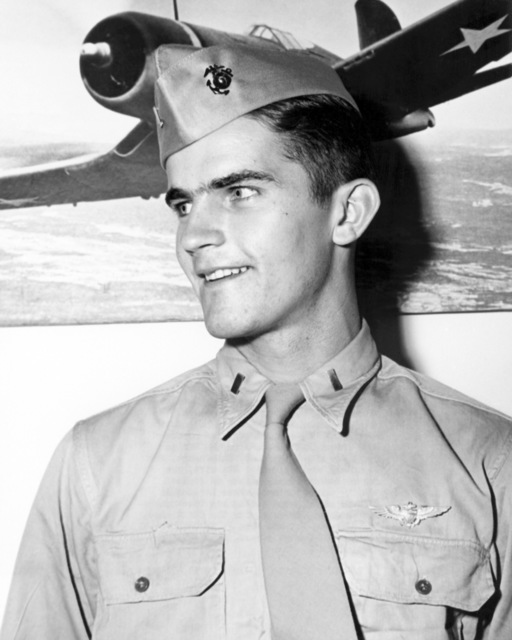 "Official Portrait of US Marine Corps (USMC) First Lieutenant (1LT) Jeremiah J. O'Keffe, taken at Marine Corps Air Depot, Miramar, San Diego, California (CA), 1945. 1LT O'Keffe is an ace pilot and is credited with 7 kills. His hometown is Ocean Springs, Mississippi. A photograph of a US Navy F4U""CORSAIR""aircraft hangs in the background.  (Exact date shot unknown)"