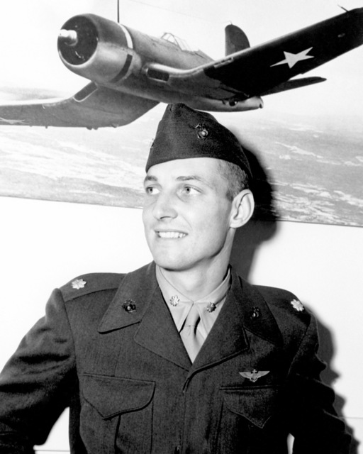 "Official Portrait of US Marine Corps (USMC) Major Jefferson D. Dorroh, Jr, taken at San Deigo, California (CA), 1945. MAJ Dorroh is an Ace Pilot credited with 6 kills. A picture of a US Navy (USN) F4U""CORSAIR""aircraft hangs in the background.  (Exact date shot unknown)"