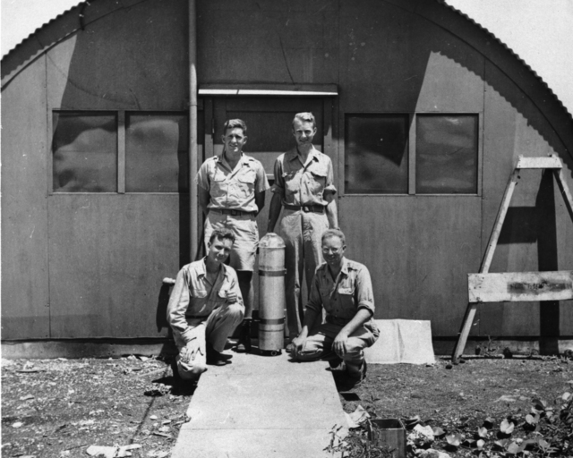 """Parachute-borne pressure gauge, Tinian Island, Marianas with """"scientific observers"""" of the 509th group, 1945. Luis Alvarez (standing, right). Copied from Luis Alvarez' personal photos. Morgue 1946-8 (P-13); ZN 3284 [photographer unknown]"""