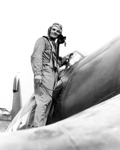"World War II (WWII) era photograph of US Marine Corps (USMC) First Lieutenant (1LT) Williams L. Hood, standing on the wing of a US Navy (USN) F4U""CORSAIR""aircraft at Okinawa, Japan, 1945. 1LT Hood is an Ace Pilot credited with 5 kills.  (Exact date shot unknown)"