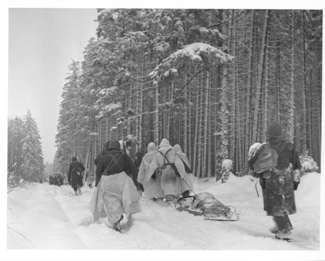 Photograph of American Troops Dragging a Heavily Loaded Ammunition Sled as the Move from an Attack on Herresbach, Belgium