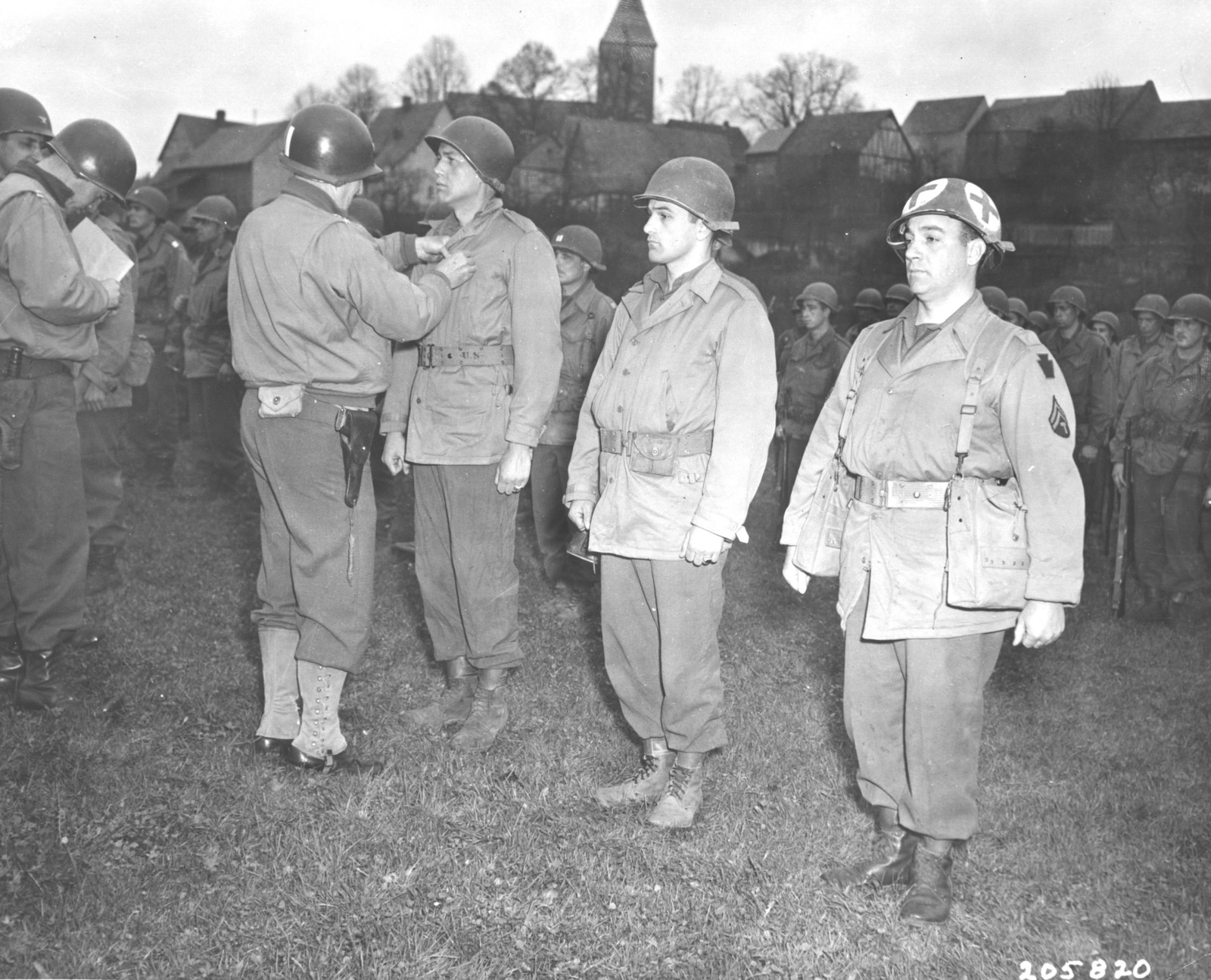 Photograph of Major General Norman Cota Presenting the Bronze Star Medal to Corporal John H. Reese, Corporal Harry D. McMahan and Tec 5 Ernest Geibel