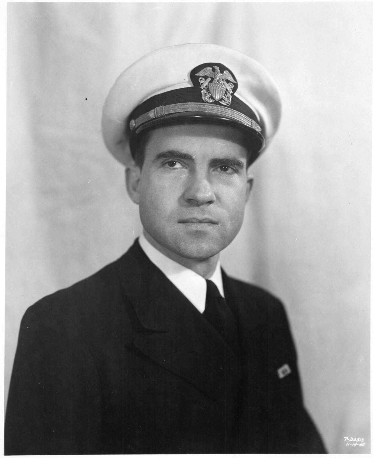 Formal portrait of Lt. Commander Richard Nixon wearing a coat and Navy hat