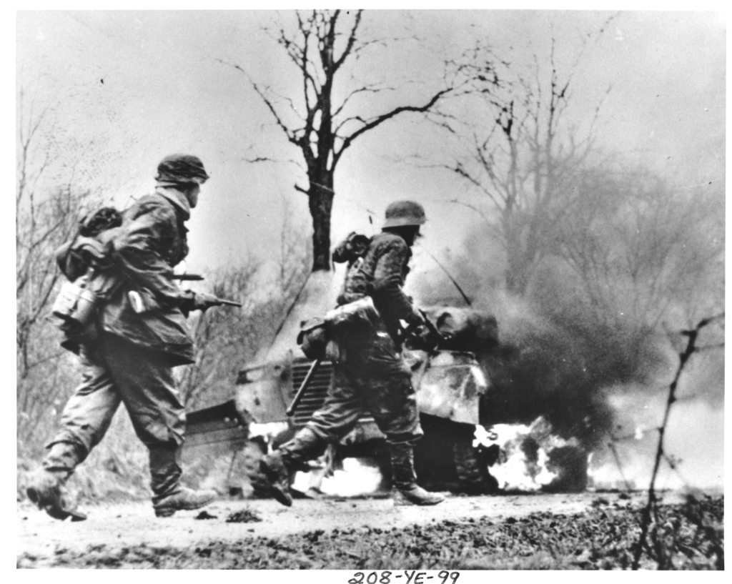 Photograph taken from Captured German Film of German Troops Advancing Past Burning American Equipment