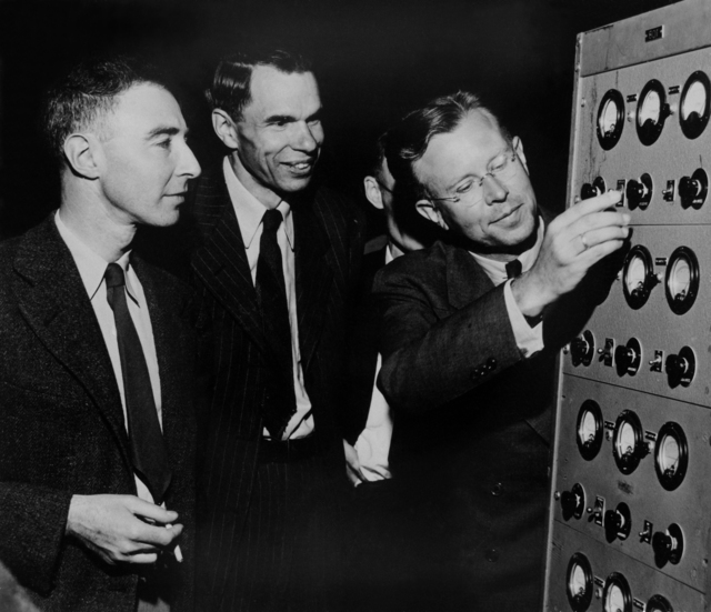 Ernest O. Lawrence, Glenn T. Seaborg, and J. Robert Oppenheimer in early 1946 at the controls to the magnet of the 184-inch cyclotron, which was being converted from its wartime use to its original purpose as a cyclotron. Morgue 1946-12 (P-1) [Photographer: Donald Cooksey]