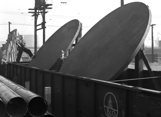 """184-inch cyclotron plates at Southern Pacific freight yard, Donald Cooksey standing at left. Photo taken 1/14/1946. 184""""-139. Principal Investigator/Project: Analog Conversion Project"""
