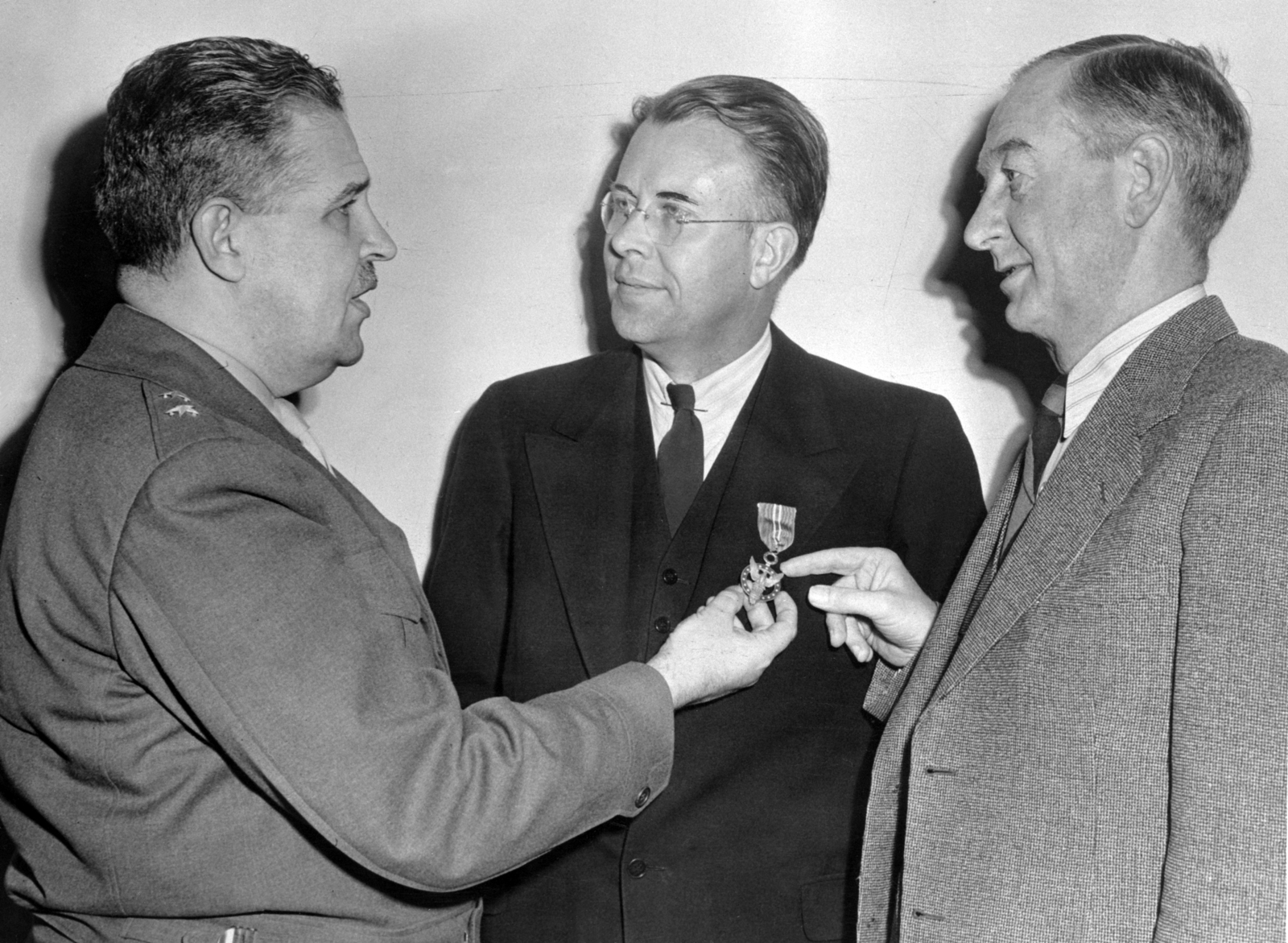 General Groves (left) and University of California, Berkeley President Robert Gordon Sproul (right) admire the Medal of Merit awarded to Ernest Orlando Lawrence in March, 1946 for his wartime achievements. Morgue 1958-8 (P-30) [Photographer: Donald Cooksey]