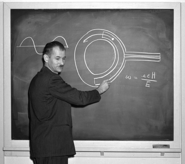 Edwin McMillan at blackboard with cyclotron drawing on board. Picture taken at the time of the release of the Synchrotron story. Negative envelope dated April 30, 1946. Morgue 1946-10(P-1), XBB6708-04860, and Cooksey 706B [Photographer: Donald Cooksey]