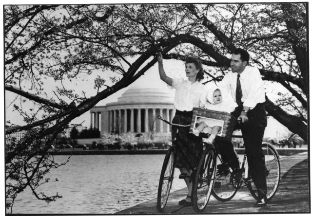 Richard and Pat Nixon take a bicycle ride with their baby daughter Tricia after arriving in Washington, D.C