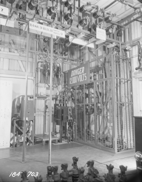 """184-inch cyclotron. Main 12 K.V. switching area in M.G. room. 12 K.V. main O.C.B. on termination of 6,200 K.V. A line from campus, on right. 12 K.V. O.C.B. for transformers feeding 2,300 volt bus. on left. Metering transformers inside cage. Fused disconnects on overhead 12 K.V. distribution bussrs. Photo taken 3/15/1947. 184""""-703 Principal Investigator/Project: Analog Conversion Project"""