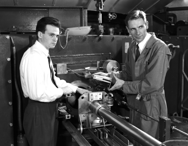 The discovery of machine-made mesons by Lattes and Gardner was announced. in February , 1948. C.M.G. Lattes (left) and E. Gardner with the emulsion positioning apparatus for the 184-inch meson experiments taken. March 8, 1948. Morgue 1948-4 (P-3) [Photographer: Donald Cooksey]