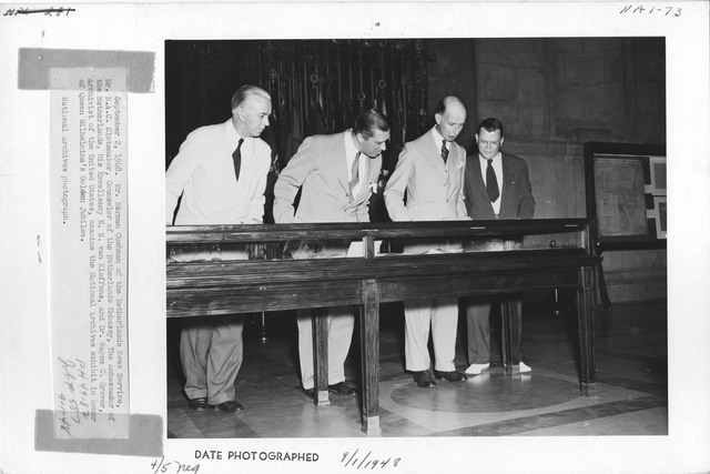 Photograph of Mr. Norman Cushman of the Netherlands News Service, Dr. N. C. Slotemaker, Counselor of the Netherlands Embassy, the Ambassador of the Netherlands, His Excellency E. N. van Kleffens, and Dr. Wayne C. Grover, Archivist of the United States, Examining the National Archives Exhibit in Honor of Queen Wilhelmina's Golden Jubilee