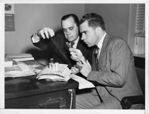 "Richard Nixon and Robert Stripling examine ""pumpkin papers"" microfilm obtained from Whittaker Chambers"