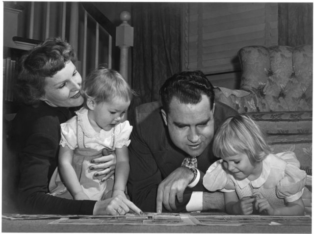 Richard and Pat Nixon view pages spread on the floor with their two young daughters in Alexandria, Virginia