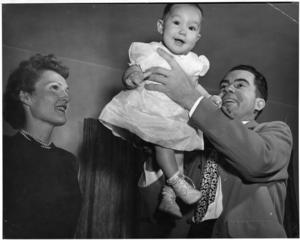 Richard Nixon holds his baby daugher Julie in the air. Pat Nixon watches from his side