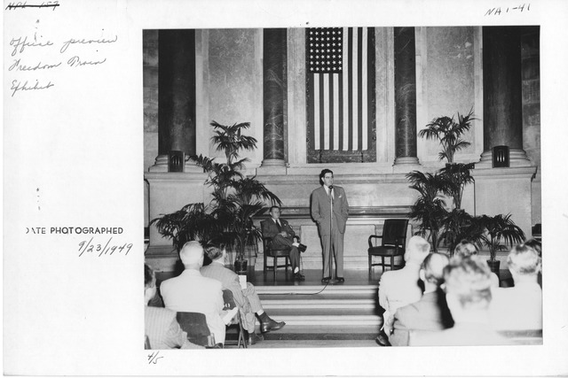 Photograph of Official Preview Freedom Train Exhibit: General Services Administration (GSA) Administrator Jess Larson speaking, Dr. Wayne C. Grover, Archivist of the United States, seated