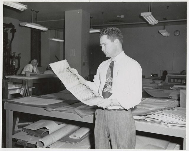 Photograph of National Archives Employee Bob Linden Holding Repaired and Laminated Documents Scorched in Chicago Fire