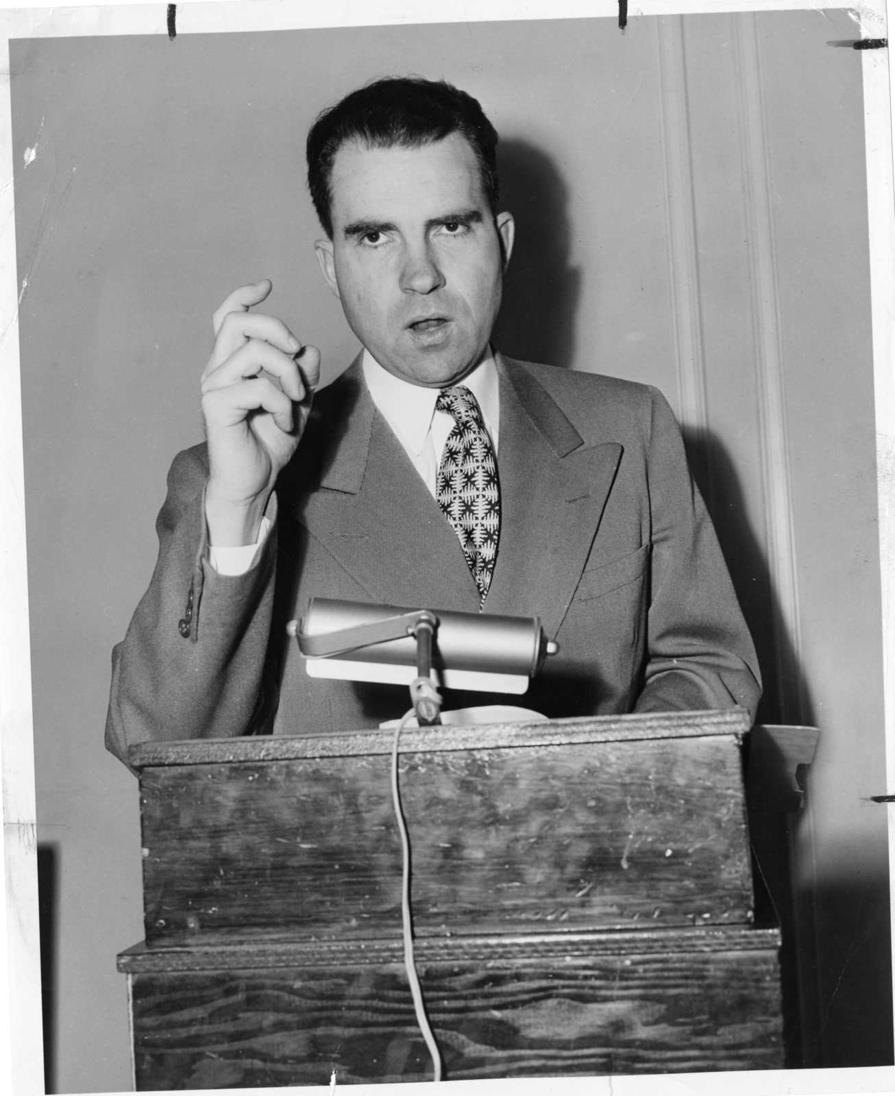 Richard Nixon stands behind a podium and speaks during his Senatorial campaign