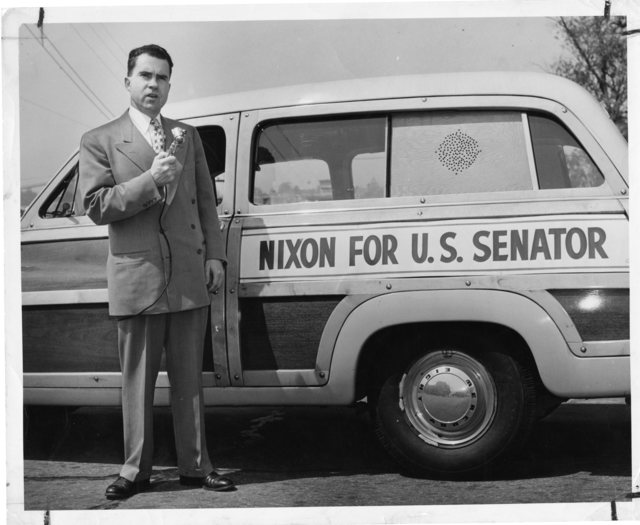 "Richard Nixon stands in front of his campaign automobile and holds a microphone. A sign on the automobile reads: ""Nixon for U.S. Senator."""