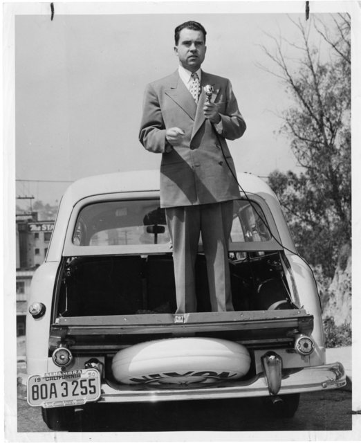 "Richard Nixon stands on the trunk of his campaign automobile. A sign on the automobile reads: ""Nixon for U.S. Senator."""