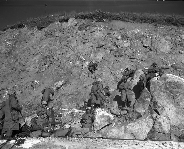 First Marine Division Infantrymen Take to a Rugged Hillside in Wiping Out Enemy Troops Who Have Set up a Road Block Against the Allied Advance