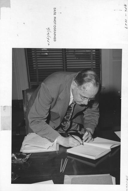 Photograph of Dr. Solon J. Buck Inscribing Copy of Archivium
