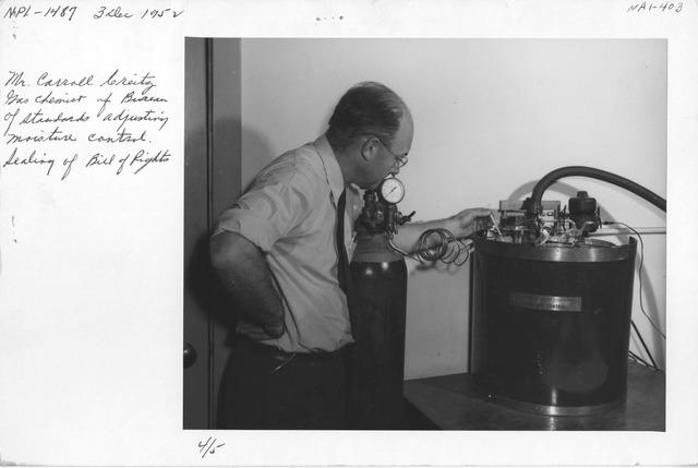 Photograph of Mr. Carroll Creitz, Gas Chemist of Bureau of Standards Adjusting Moisture Control Sealing of Bill of Rights