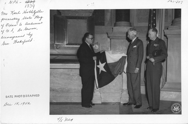 Photograph of Mr. Karl Hoblitzelle Presenting State Flag of Texas to the Archivist of the United States, Dr. Wayne Grover, Accompanied by Senator Paul Wakefield