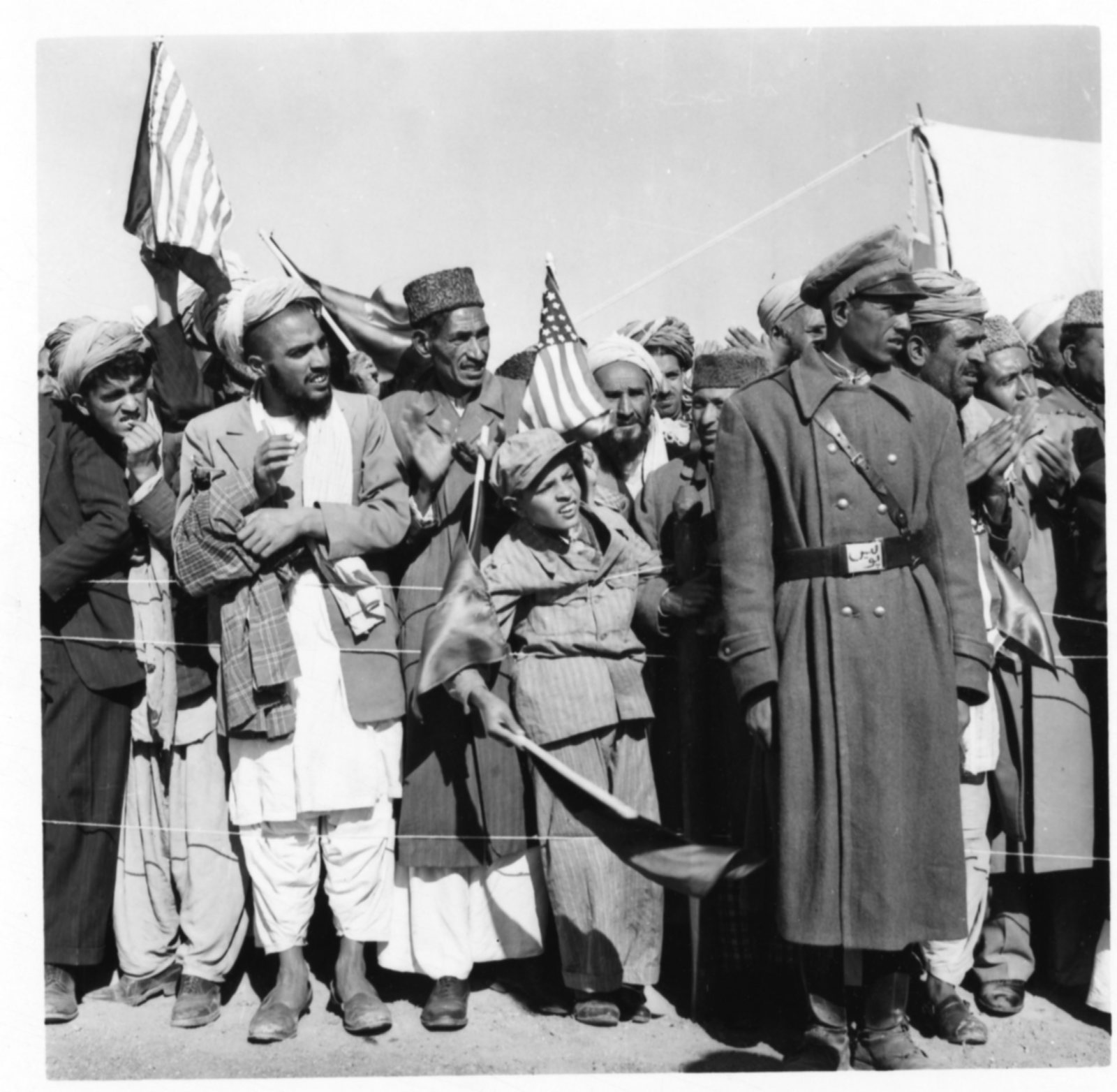Spectators holding flags await the arrival of Vice President Richard Nixon in Afghanistan