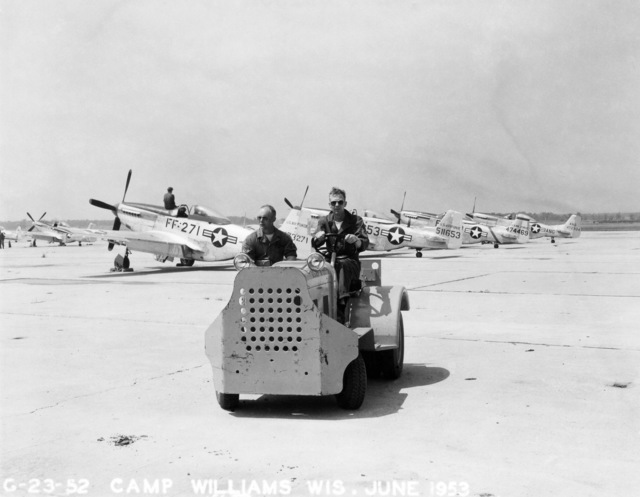 """U.S. Air Force maintenance personnel assigned to the 119th Fighter Wing""""Happy Hooligans"""", North Dakota Air National Guard, operate an aircraft two tractor near F-51D Mustang aircraft at Camp Williams, Wisconsin in 1953. (A3604) (U.S. Air Force PHOTO) (Released)"""
